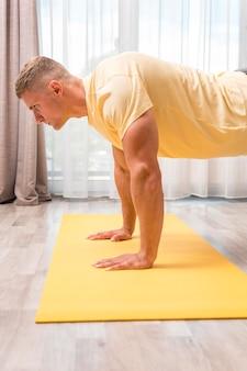 Человек занимается фитнесом дома на коврике