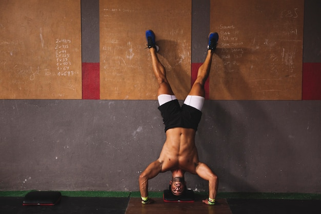Man doing handstand in gym