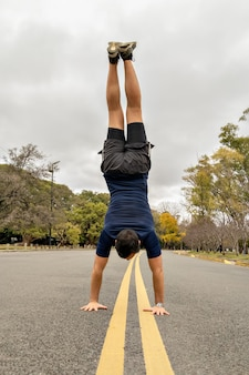 Man doing a handstand in the middle of the road