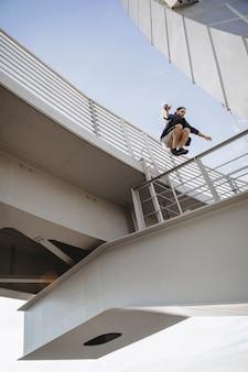 Man doing huge parkour jump from the bridge
