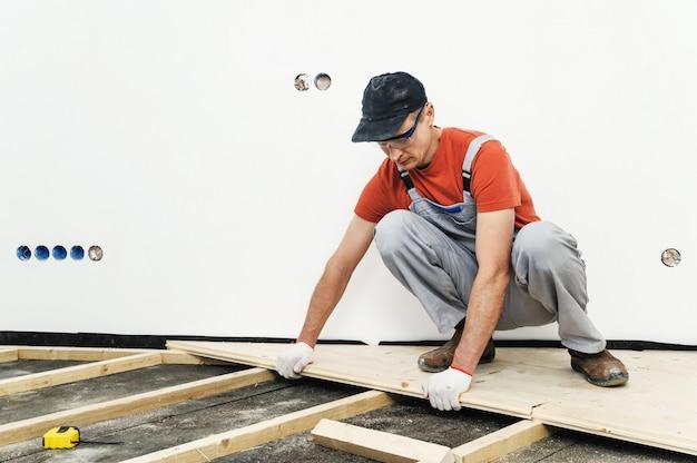 木の床のインストールをしている男。