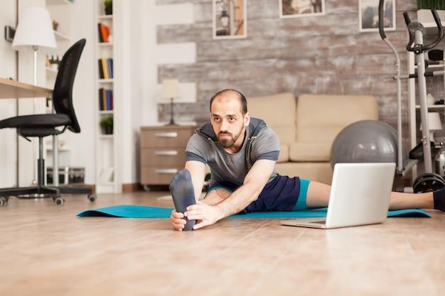Мужчина делает растяжку ног на коврике для йоги после онлайн-тренировки во время глобальной изоляции.