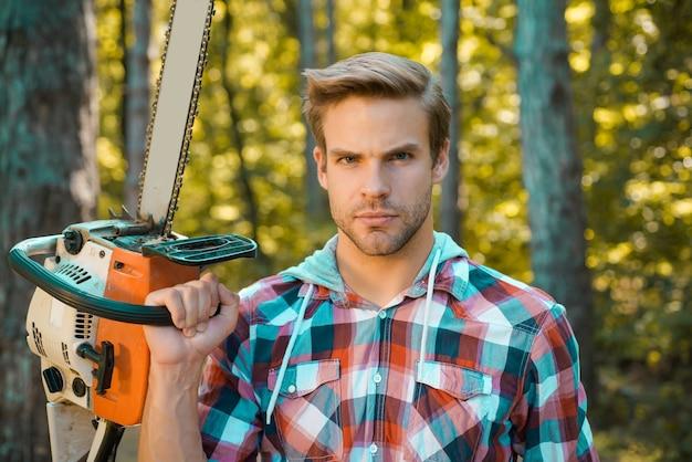 Человек, выполняющий мужскую работу, лесоруб с серьезным лицом несет бензопилу, вырубка лесов - основная причина зем ...