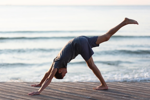 Man doing one legged downward dog pose outside