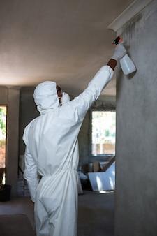 남자는 벽에 해충 방제를 하 고