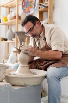 Uomo che fa la ceramica per divertimento