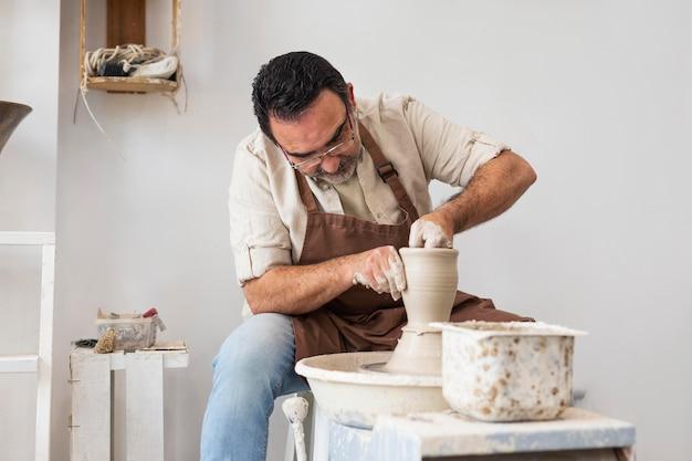 Человек делает керамику в помещении средний план