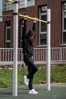 Man doing pull ups on the horizontal bar while training at evening outdoors strong athlete in tracksuit doing exercise at street gym apparatus