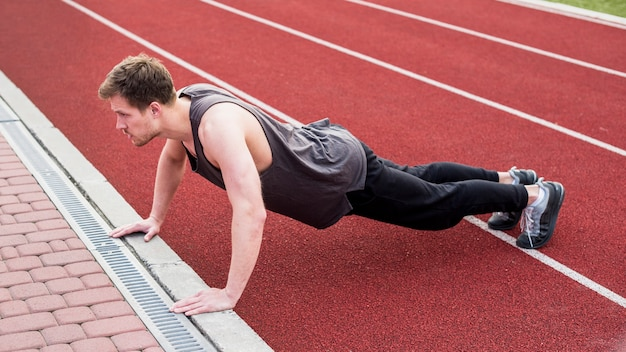 Man doing push ups exercise on race track
