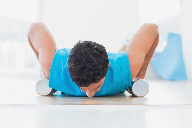 Человек делает push ups с гантелями в фитнес-студии
