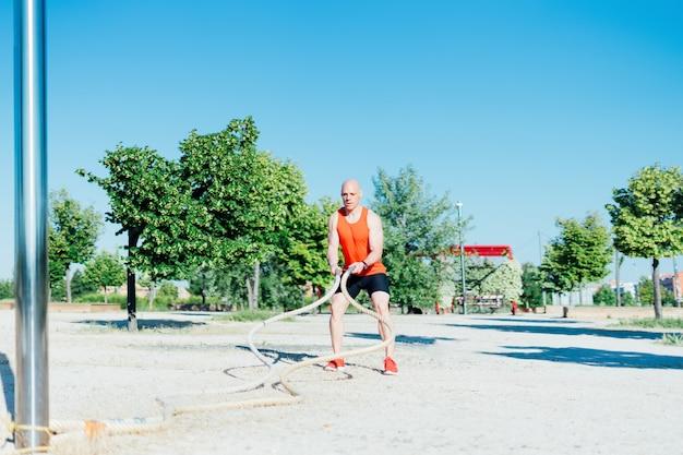 屋外でロープ運動をしている男。