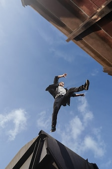 Man doing scary jump between roofs. guy practicing parkour free running.