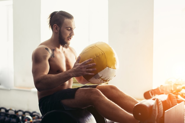 Человек делает sit ups с шариком медицины на скамейке, работает на мышцы живота