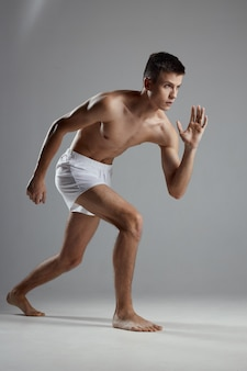 傾いて白いパンツで屋内でスポーツをしている男