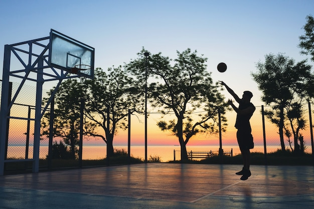 Man doing sports, playing basketball on sunrise, jumping silhouette