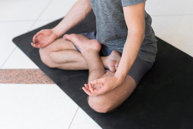 Man doing sukhasana pose on mat inside