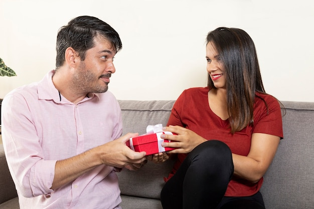 Man doing suspense to deliver present to his wife.