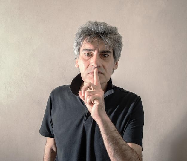 Человек делает жест молчания
