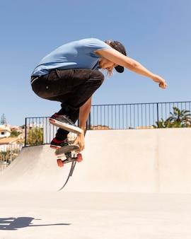 Человек делает трюк на скейтборде полный кадр