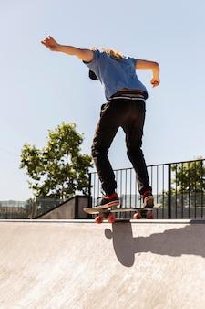 スケートボードのフルショットでトリックをしている男