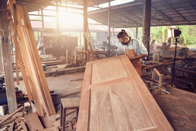 Человек делает столярные изделия в плотницких работах. плотник по деревянной доске в мастерской, винтажный стиль