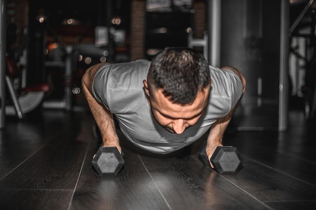重いダンベルでトレーニングをしている男。ロフトのインテリアの床で運動しながら、スポーツウェアを着て板の位置をしている自信を持って筋肉質の若い男。