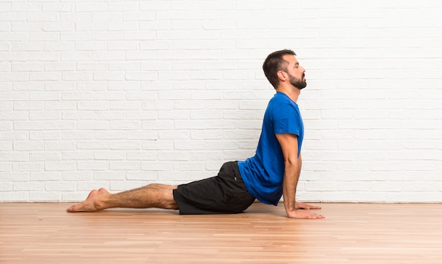 Man doing yoga exercises indoors
