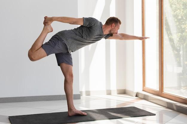 Man doing yoga indoor looking through window
