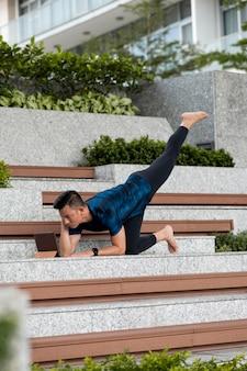 階段でヨガをしている男