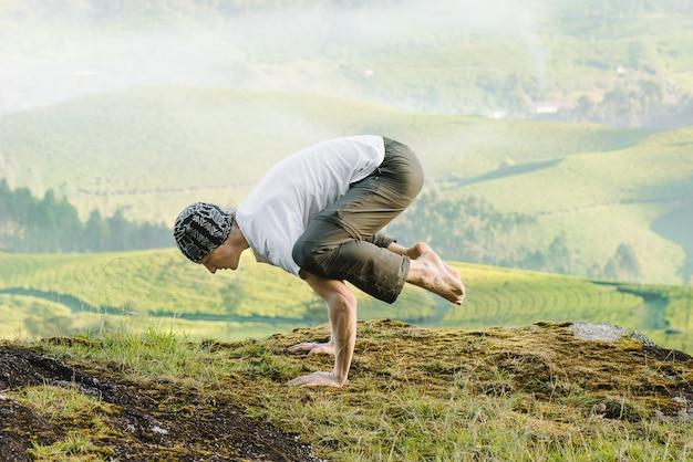 朝、山で屋外でヨガをしている男。