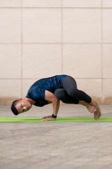Uomo che fa yoga all'aperto sulla stuoia