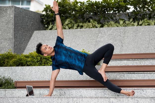 Man doing yoga on steps outdoors