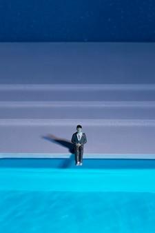 スイミングプールの隣に座っている男の人形