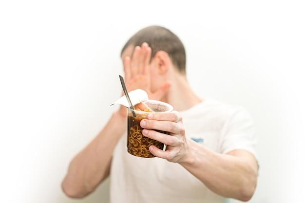 Человек не хочет смотреть на прозрачный пластиковый стаканчик лапши быстрого питания на белом фоне.
