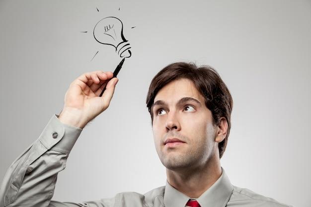 남자가 아이디어가있는 것처럼 머리 위에 램프를 그립니다.
