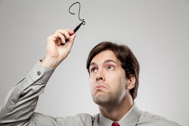 의심스러운 것처럼 머리 위에 물음표를 그리는 남자.