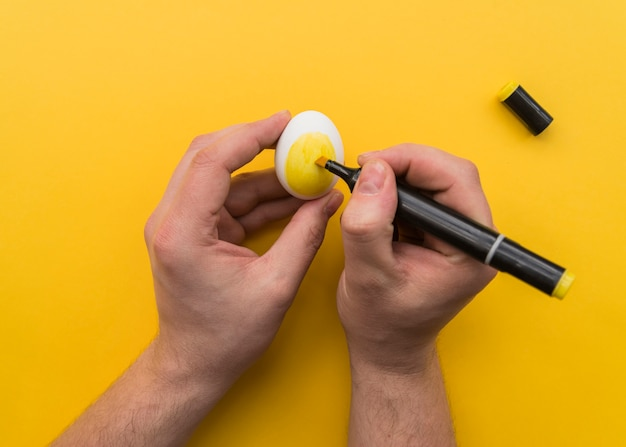 Man drawing on egg