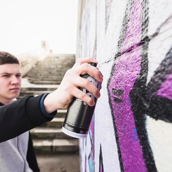 Человек рисует граффити на уличной стене