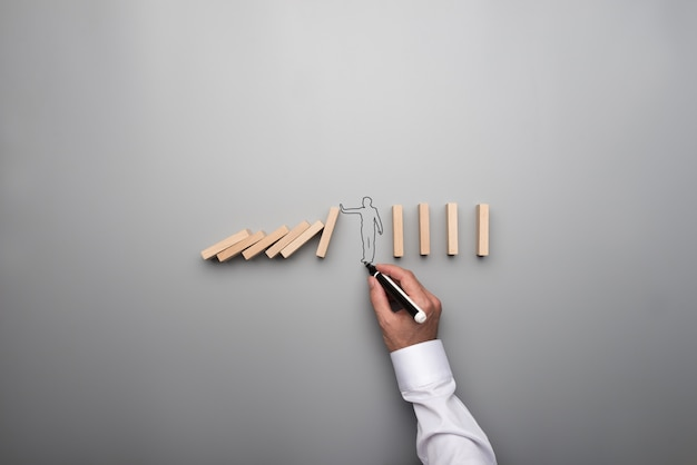 Man drawing the outline of a businessman stopping the domino effect