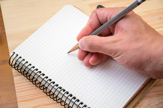 Man drawing something in notebook on placed table