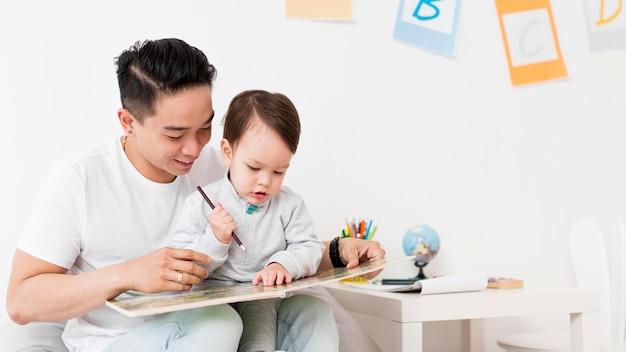 Человек рисует с ребенком дома