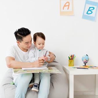 Человек рисует с ребенком в то время как дома