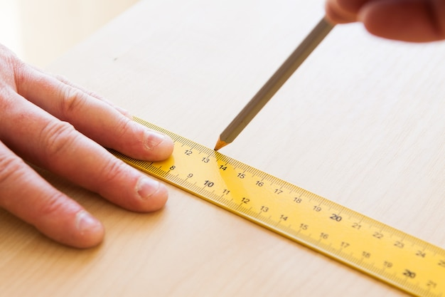 男は定規で鉛筆を描く