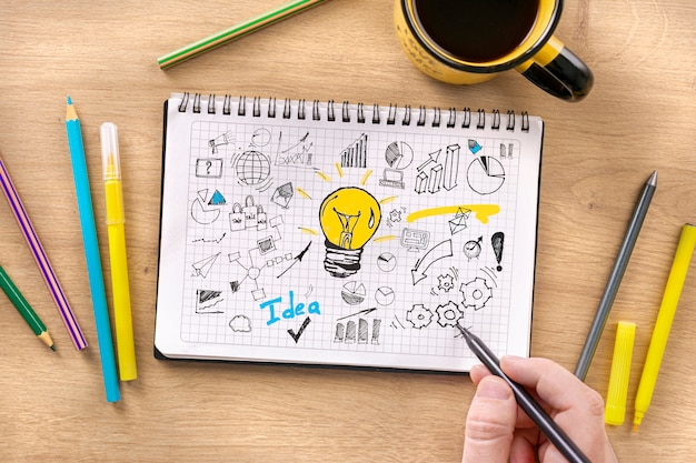 Man draws new business strategy in notebook. startup strategy development concept top view
