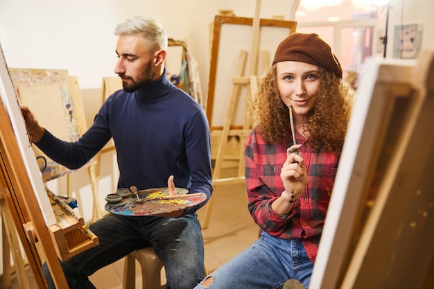 Man draws a painting and a girl smiles