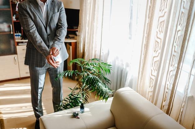 Мужчина одел куртку дома. в комнате стоит жених в строгом костюме. закройте вверх. концепция одежды. жених в свадебное утро.