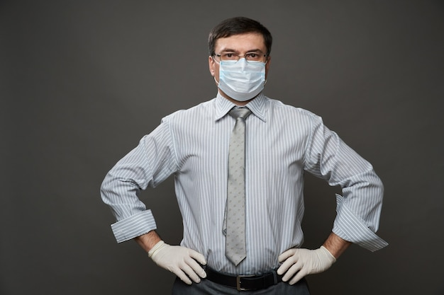 A man dressed as a businessman, posing in studio on gray background, medical face mask and protective gloves, glasses, shirt and tie - concept of quarantine and antivirus protection