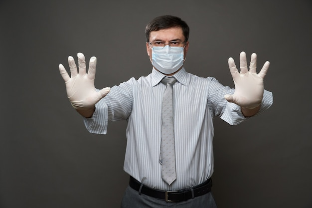 A man dressed as a businessman showing stop with the palm of his hand, gray background, medical face mask and protective gloves, glasses, shirt and tie - concept of quarantine and antivirus protection