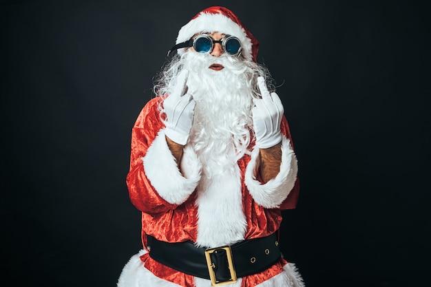 サンタクロースに扮した男が失礼なジェスチャーをし、黒い背景に「ファックユー」のサインとして指を上げます。クリスマスのコンセプト、サンタクロース、ギフト、お祝い。
