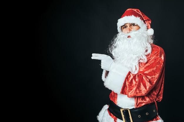Человек, одетый как санта-клаус, указывая налево с копией пространства, на черном фоне. рождественские концепции, санта-клаус, подарки, праздник.